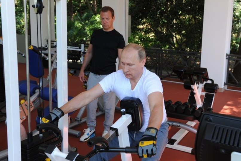 Russias President Vladimir Putin (C) and Russian Prime Minister Dmitry Medvedev work out at a gym at the Bocharov Ruchei state residence in Sochi on August 30, 2015. AFP PHOTO / RIA NOVOSTI / MIKHAIL KLIMENTYEV (Photo credit should read MIKHAIL KLIMENTYEV/AFP/Getty Images)