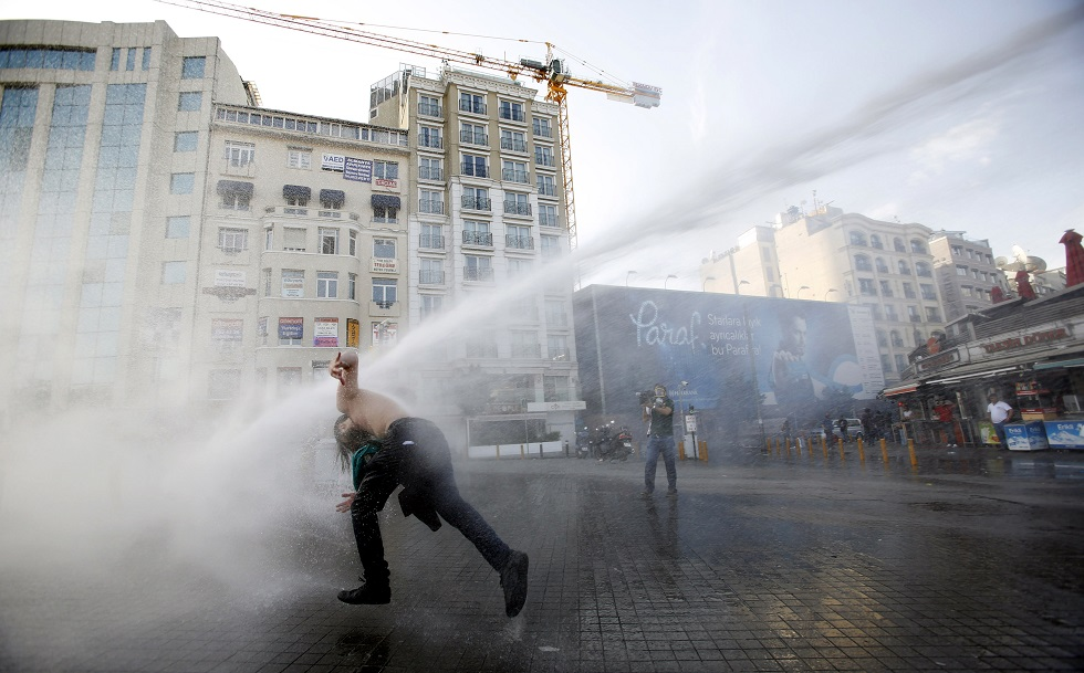 Turkish riot police use water cannon to disperse demonstrators during a protest against the destruction of trees in a park brought about by a pedestrian project, in Taksim Square in central Istanbul May 31, 2013. REUTERS/Murad Sezer (TURKEY - Tags: POLITICS CIVIL UNREST ENVIRONMENT CRIME LAW TPX IMAGES OF THE DAY) - RTX106VO