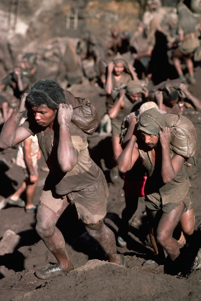 "August 1985, Brazil --- 70,000 workers or hormigueros, ""ants"", carry sacks of dirt down the mountain at the Serra Pelada, or Naked Mountain, gold mine in Brazil. The dirt is sifted at the bottom of the mountain for gold nuggets. --- Image by © Stephanie Maze/CORBIS"