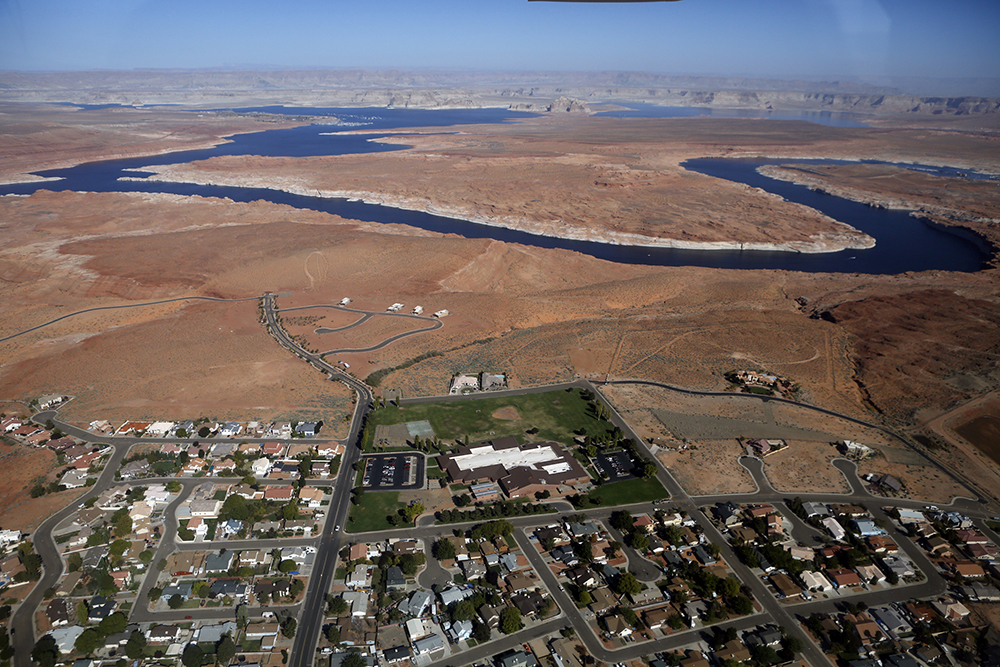 Lake Powell and nearby surburbs is seen from an Eco-Flight plane giving students tours, looking at water and energy issues along the Upper Colorado River. The Glen Canyon Dam was built to store water inaddition to providing power for states down river making Lake Powell. When the lake is full 3 to 4 percent of the water is lost due to evorporation. Photo by Heather Rousseau, courtesy of Eco-Flight