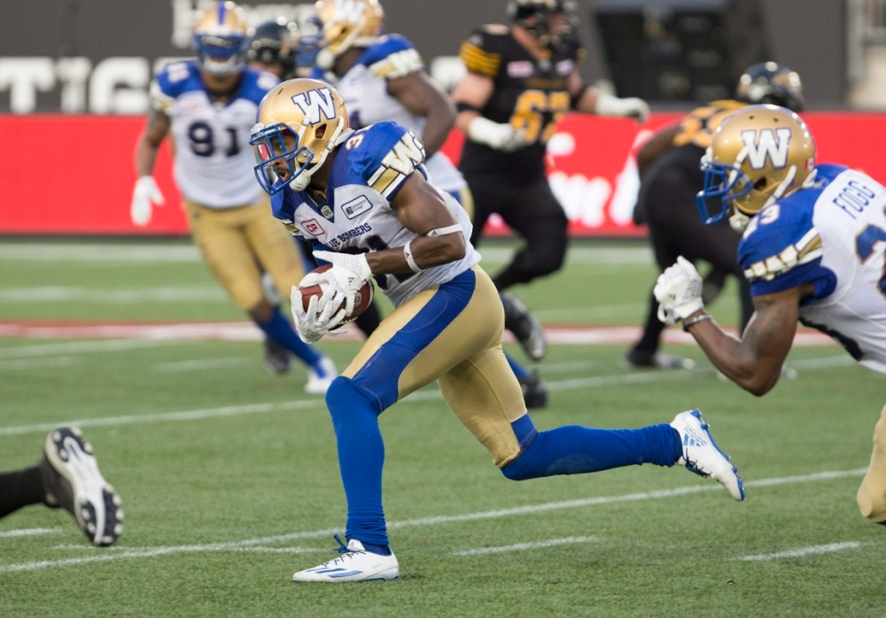 Winnipeg Blue Bombers defensive back Maurice Leggett (31) heads for the end zone for a touchdown following an interception against the Hamilton Tiger-Cats during the first half of CFL football action in Hamilton on Thursday, July 7, 2016. THE CANADIAN PRESS/Peter Power
