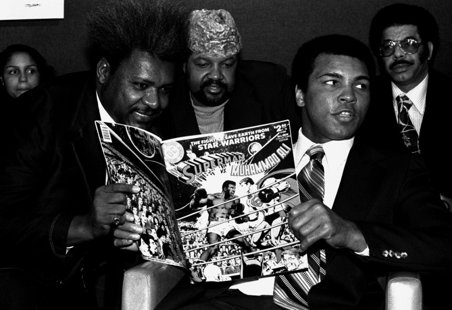 World heavyweight champion Muhammad Ali, right, is shown at a press conference in New York, January 31, 1978, with promoter Don King, left, and Herbert Muhammad, center, to plug a comic book in which he beats Superman.  Ali holds a copy of the comic book.  (AP Photo/Marty Lederhandler)