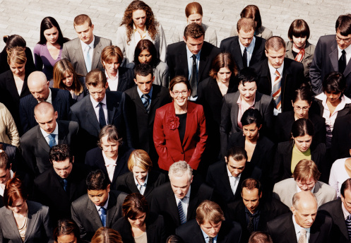 Businesswoman in a Red Suit Standing Out in a Crowd of Businesspeople in Black and Grey Suits