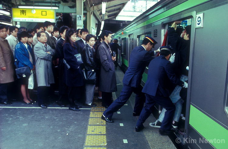 Japanese commuters wait in line for the next train, while people pushers push passengers onto the Yamanote line subway train during the morning rush hour at Shinjuku station in Tokyo, Japan. The daily ritual is performed to maximize the number of commuters on trains.
