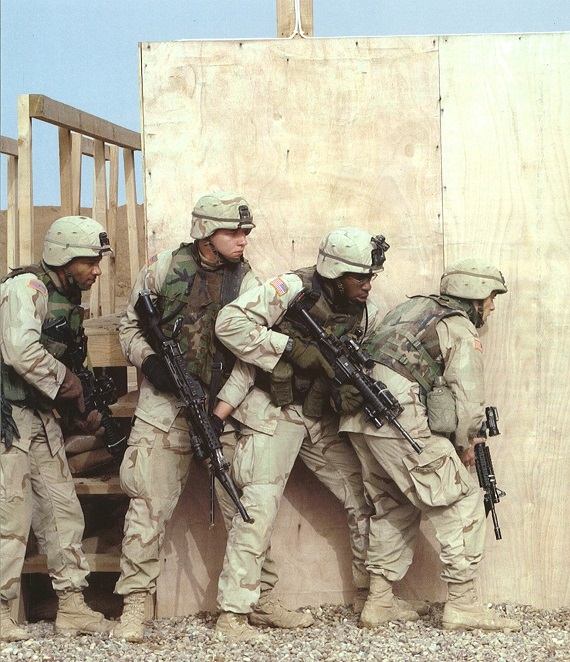 Soldiers practice house-breaching techniques in their desert combat uniforms. (Photo courtesy of the U.S. Army)